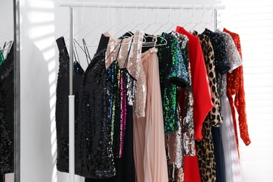 Different stylish women's clothes on rack indoors