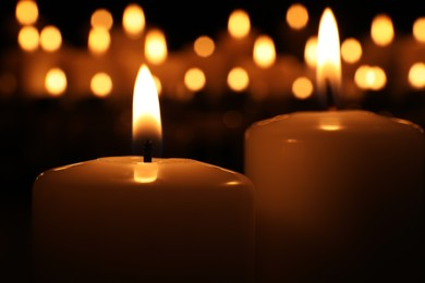 Burning candles in darkness, closeup. Memory day