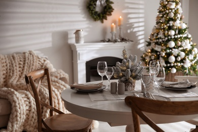 Festive table setting and beautiful Christmas decor in living room. Interior design