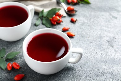 Fresh rose hip tea and berries on grey table, closeup. Space for text