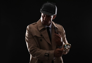 Old fashioned detective with smoking pipe and magnifying glass on dark background