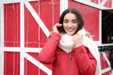 Young woman spending time at winter fair. Christmas celebration