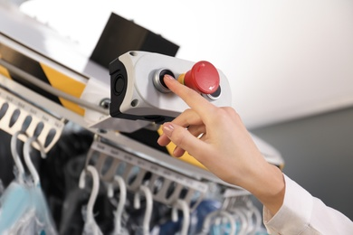 Worker pressing button on control panel of garment conveyor at modern dry-cleaner's, closeup