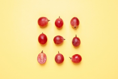 Flat lay composition with fresh ripe grapes on yellow background