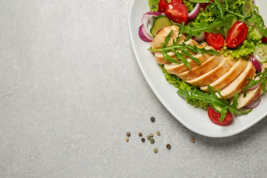 Delicious salad with meat, arugula and vegetables on grey table, flat lay. Space for text