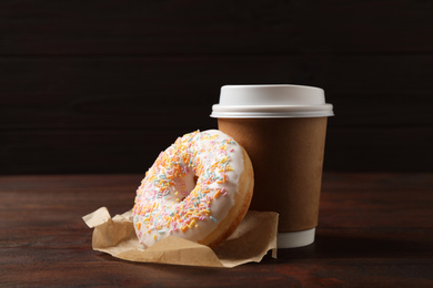 Yummy donut and paper cup on wooden table against brown background