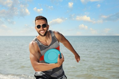 Happy man throwing flying disk at beach on sunny day