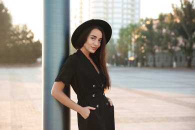 Beautiful young woman in stylish black dress and hat on city street
