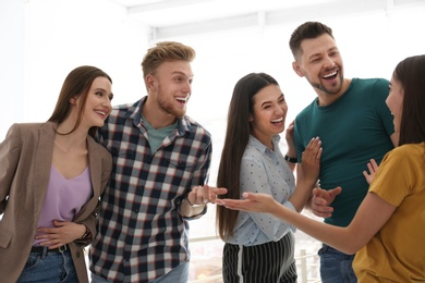 Group of happy people talking in light room