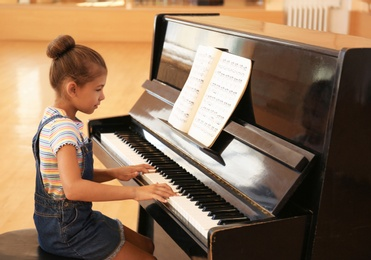 Cute little girl playing piano indoors. Music lesson