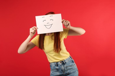 Woman hiding behind sheet of paper with happy face on red background