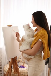 Beautiful young woman drawing on easel with cat at home