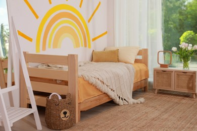 Cute child's room interior with bed and sun art on wall