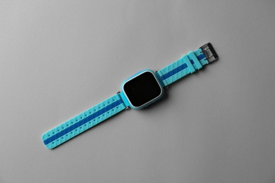 Trendy smart watch for kids on grey background, top view