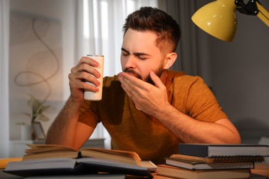 Tired young man with energy drink studying at home