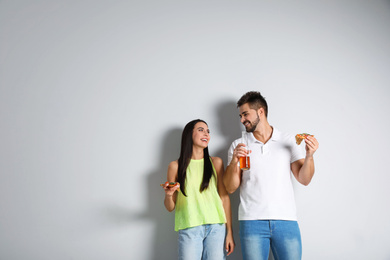 Happy couple with pizza and beer on white background, copy space text