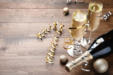 Glasses and bottle of champagne, serpentine streamers with Christmas balls on wooden table. Space for text