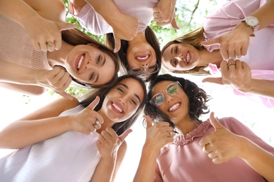 Happy women showing thumbs up outdoors, bottom view. Girl power concept