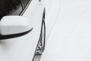 Modern car leaving tire track on snowy road, closeup view