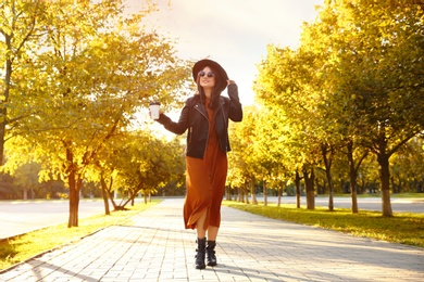 Beautiful young woman with cup of coffee wearing stylish clothes in autumn park