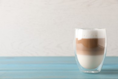 Glass of delicious layered coffee on turquoise wooden table against white background, space for text