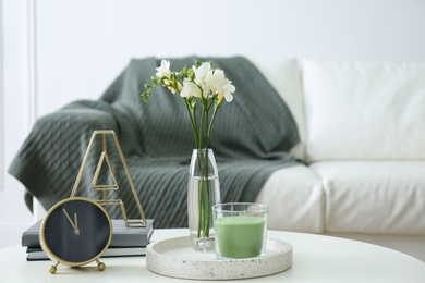 Vase with beautiful freesia flowers, candle and clock on table indoors, space for text. Interior elements