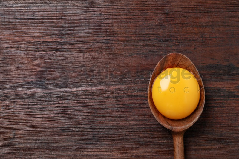 Spoon with raw egg yolk on wooden table, top view. Space for text