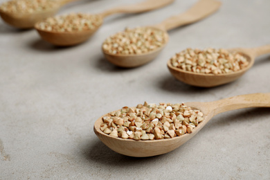 Uncooked green buckwheat grains in spoons on light table