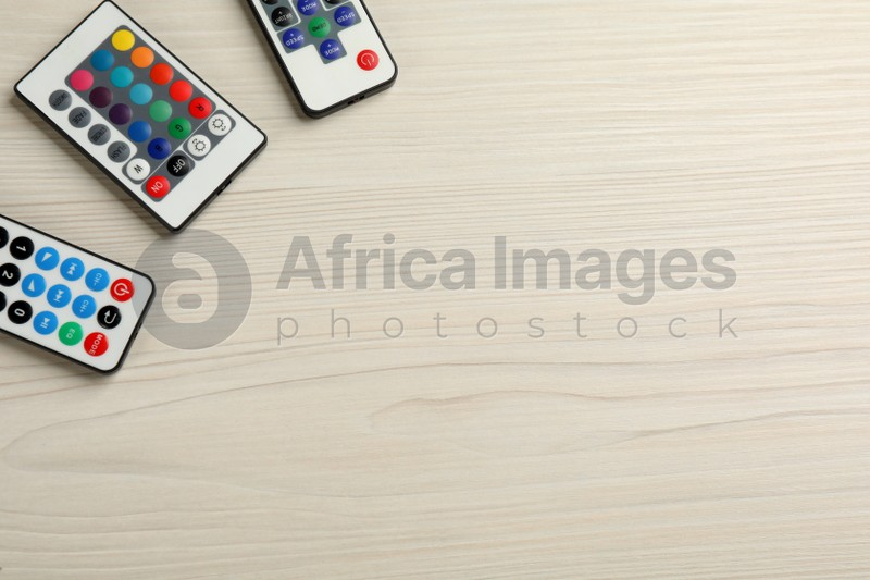 Remote controls on white wooden table, flat lay. Space for text
