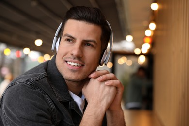 Handsome man with headphones listening to music in outdoor cafe, space for text