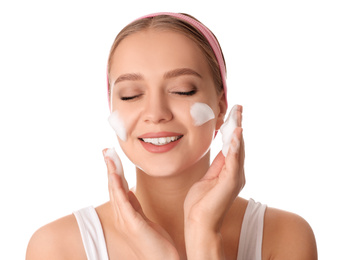 Young woman washing face with cleansing foam on white background. Cosmetic product
