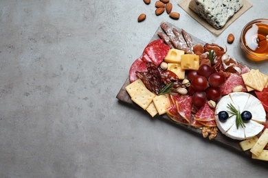 Wooden board with different appetizers on grey table, flat lay. Space for text