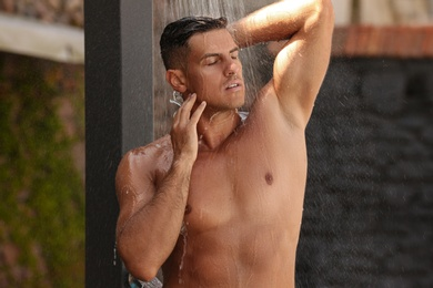 Man washing hair in outdoor shower on summer day