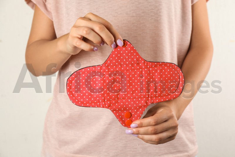 Woman holding reusable cloth menstrual pad isolated on white, closeup