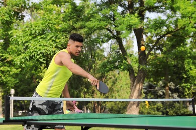 Handsome man playing ping pong outdoors on summer day