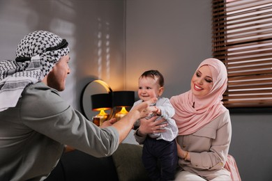 Happy Muslim family with little son in living room