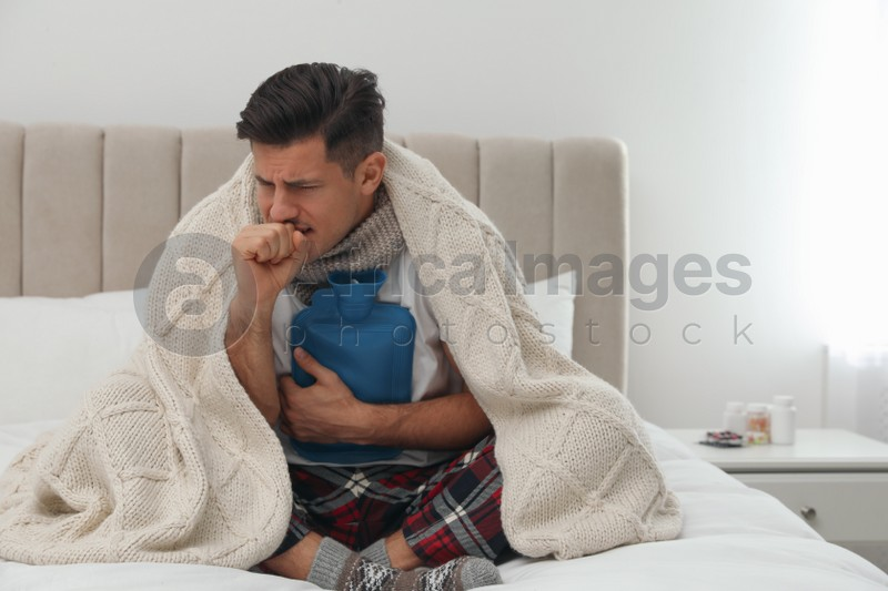 Ill man with hot water bottle coughing at home