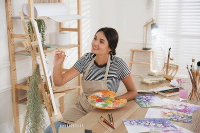 Young woman drawing on easel with brush, closeup