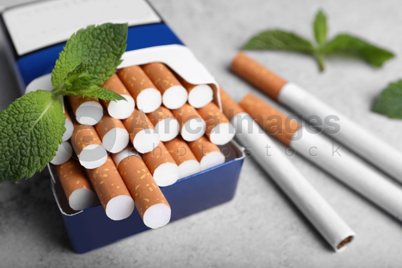 Pack of menthol cigarettes and mint leaves on grey table, closeup