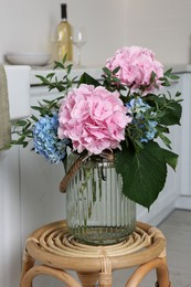 Beautiful hortensia flowers in vase on stand indoors