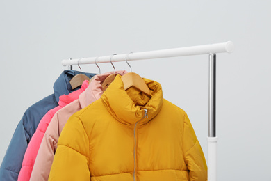 Rack with warm jackets on light background