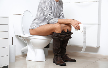 Man with paper roll sitting on toilet bowl in bathroom, closeup