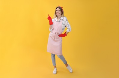 Young housewife in gloves on yellow background