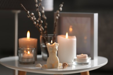 Beautiful body shaped candles and willow bouquet on table indoors