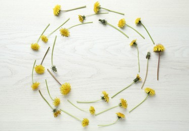Frame of beautiful yellow dandelions on white wooden table, flat lay. Space for text
