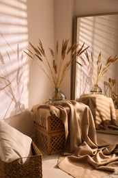 Vase with decorative dried plants and painting in stylish room interior