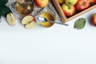 Natural apple vinegar and fresh fruits on white wooden table, flat lay. Space for text