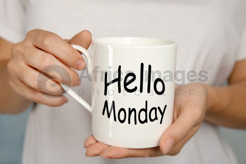 Start your week with good mood. Woman holding ceramic cup with text Hellow Monday, closeup
