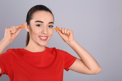 Young woman inserting foam ear plugs on grey background