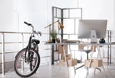 Stylish office interior with comfortable workplace and bicycle